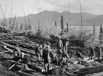 """Black soldiers serving in the Army's segregated units often didn't have enough heavy equipment, so they had to work with hand tools and their ingenuity for such tasks as building """"corduroy roads"""" with logs to stabilize the roadway through boggy muskeg areas. (Photo courtesy National Film Board of Canada)"""