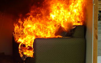A couch erupts in flame during room during a recent fire investigator training exercise at Juneau's Hagevig Regional Fire Training Center. (Photo by Matt Miller/KTOO)