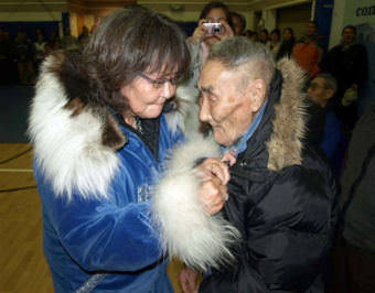 Caroline Hoover proudly pins an Alaska Territorial Guard medal on the front of her father's parka during an official discharge ceremony held Oct. 17 in Kipnuk, Alaska. David Martin is one of three surviving members of the Alaska Territorial Guard's Kipnuk unit. A total of 59 residents of Kipnuk, who volunteered to defend Alaska in the event of a Japanese invasion during World War II, were recognized during the ceremony. Kipnuk residents who served with the Alaska Territorial Guard from 1942-1947 were members of a U.S. Army component organized in response to attacks by the Japanese on Pearl Harbor. (Photo by Jerry Walton, Department of Military and Veterans Affairs cultural resource manager and native liaison/public domain/Wikimedia Commons)