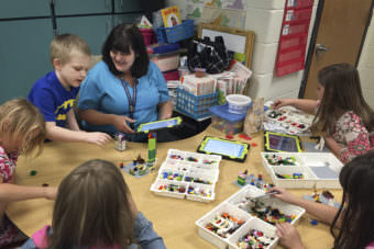 Anna Marie McClanahan (center) helps children write stories by using Legos to create scenes. (Photo by Pam Fessler, NPR)