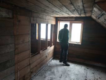 Don Andrew Roguska looks out from an upstairs window of an historic Juneau house he bought in 2016 to restore. Zoning regulations have prevented him from rebuilding in the same style. (Photo by Jacob Resneck/KTOO)