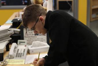 Jack Pellerin prepares his morning weather broadcast script (Photo by Wesley Early/Alaska Public Media)