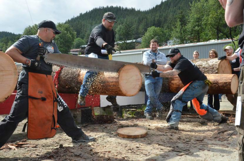 Two men compete in the team log bucking competition.