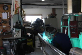 George Wilson puts the finishing touches on the second skiff Fishy Fabrications has built this spring. (Photo by KDLG)