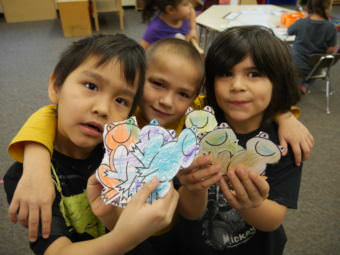 Hoonah City Schools kids showing off frogs they colored in January, 2017.