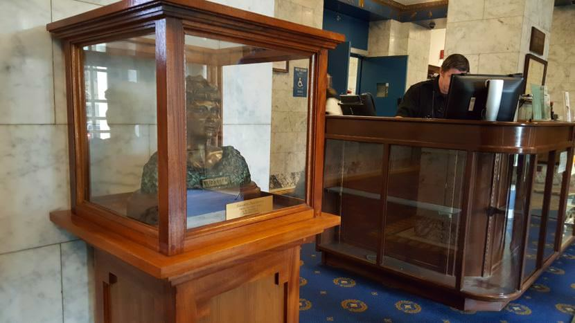 Ryan Strickland, a security and information specialist for the State of Alaska, works the front desk of the Alaska Capitol on Tuesday, July 11, 2017, in downtown Juneau. In the front lobby a bust of Alaska Native civil rights leader Elizabeth Peratrovich greets capitol visitors. (Photo by Tripp J Crouse/KTOO)
