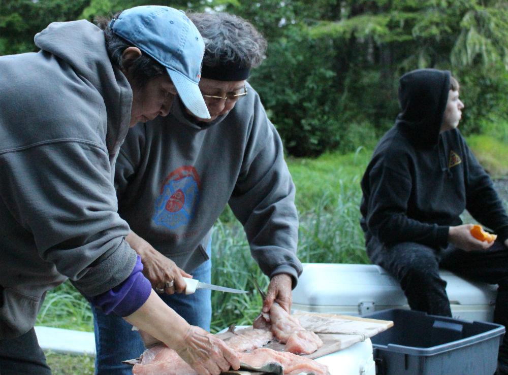 Myrna Demmert, left, works with her mom elder Ruth Demmert to filet dog salmon at Culture Camp. (Photo by Nora Saks/KFSK)