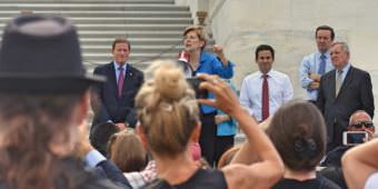 Sen. Elizabeth Warren, D-Massachusetts, addresses a crowd outside the U.S. Capitol in Washington protesting the Republican health care bill on July 25, 2017.