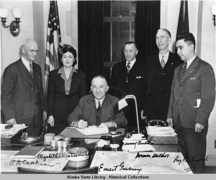 Then-Alaska Gov. Gruening signs the Anti-Discrimination Act of 1945, as O.D. Cochran, left, Elizabeth Peratrovich, Edward Anderson, Norman Walker and Roy Peratrovich stand behind him. (Photo courtesy Alaska State Library Photo Collection, P01-3294)
