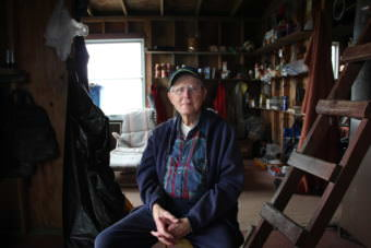 Doug Cooper sits in his cabin on Nushagak Point. (Photo by Nick Ciolino/KDLG)