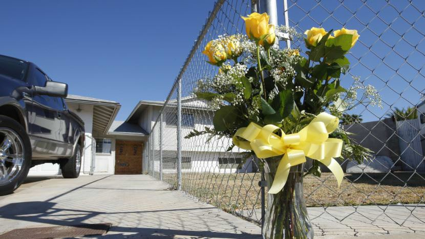 A lone bouquet of flowers stands in front of a home in Phoenix in 2013, after police said a man killed his wife, daughter and brother-in-law before killing himself. A new CDC report sheds light on patterns in homicides of women.