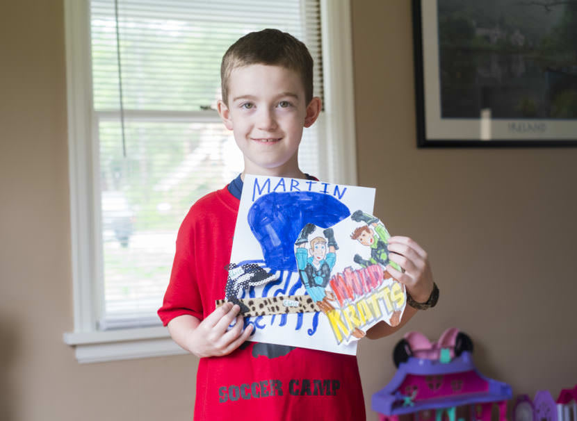 7-year-old Charlie Begenyi holds gifts for the Kratt brothers. (Photo by Annie Bartholomew/KTOO)