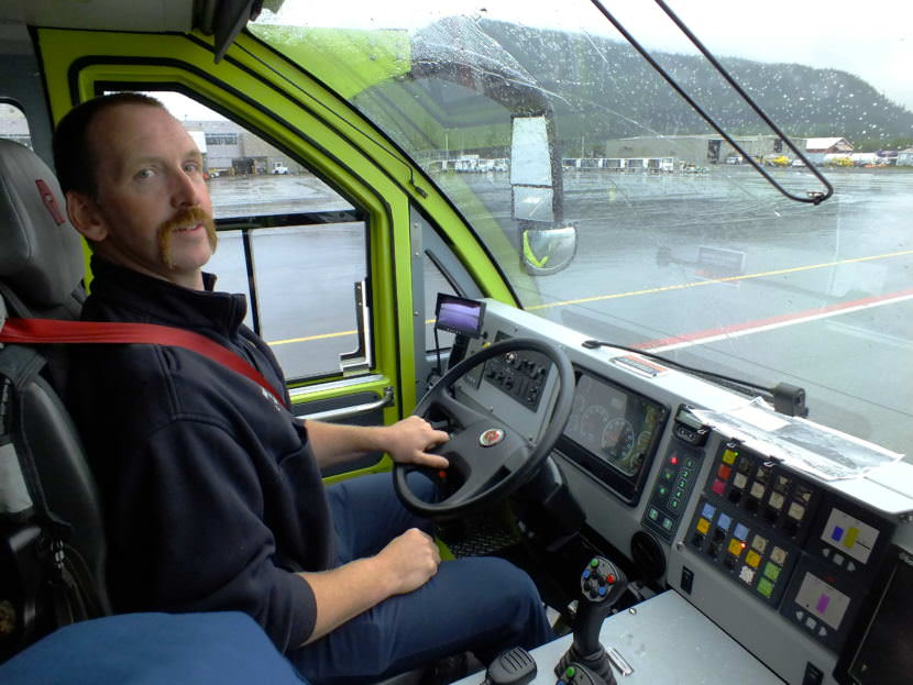 Firefighter Craig Brown in the cab of A-1, Capital City Fire/Rescue's newest Airport Rescue Firefighting (ARFF) vehicle, looks for aircraft traffic before proceeding along the 'zipper line,' special lanes for vehicle traffic at the Juneau International Airport.
