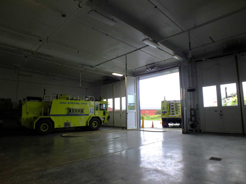 Two of Capital City Fire/Rescue's Airport Rescue Firefighting (ARFF) vehicles stand by inside and just outside of the Glacier Valley Fire Station's expanded ARFF vehicle bay.