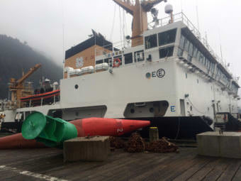 Buoys, chains and sinkers sit on the dock at Coast Guard Station Juneau with the buoy tenders Sycamore, Spar and Fir tied up in the background. (Photo by Matt Miller/KTOO)