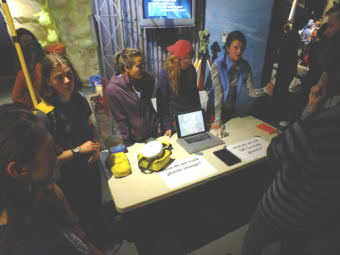 Ann Hill (left, at end of table) is wearing a yellow backpack-mounted radio antenna that was used in taking measurements of glaciers. Hill was part of the Juneau Icefield Research Program's geomatics team that surveyed ice elevation and flow during the summer of 2017, and she helped explain their research during a recent open house at the Mendenhall Glacier Visitor Center.