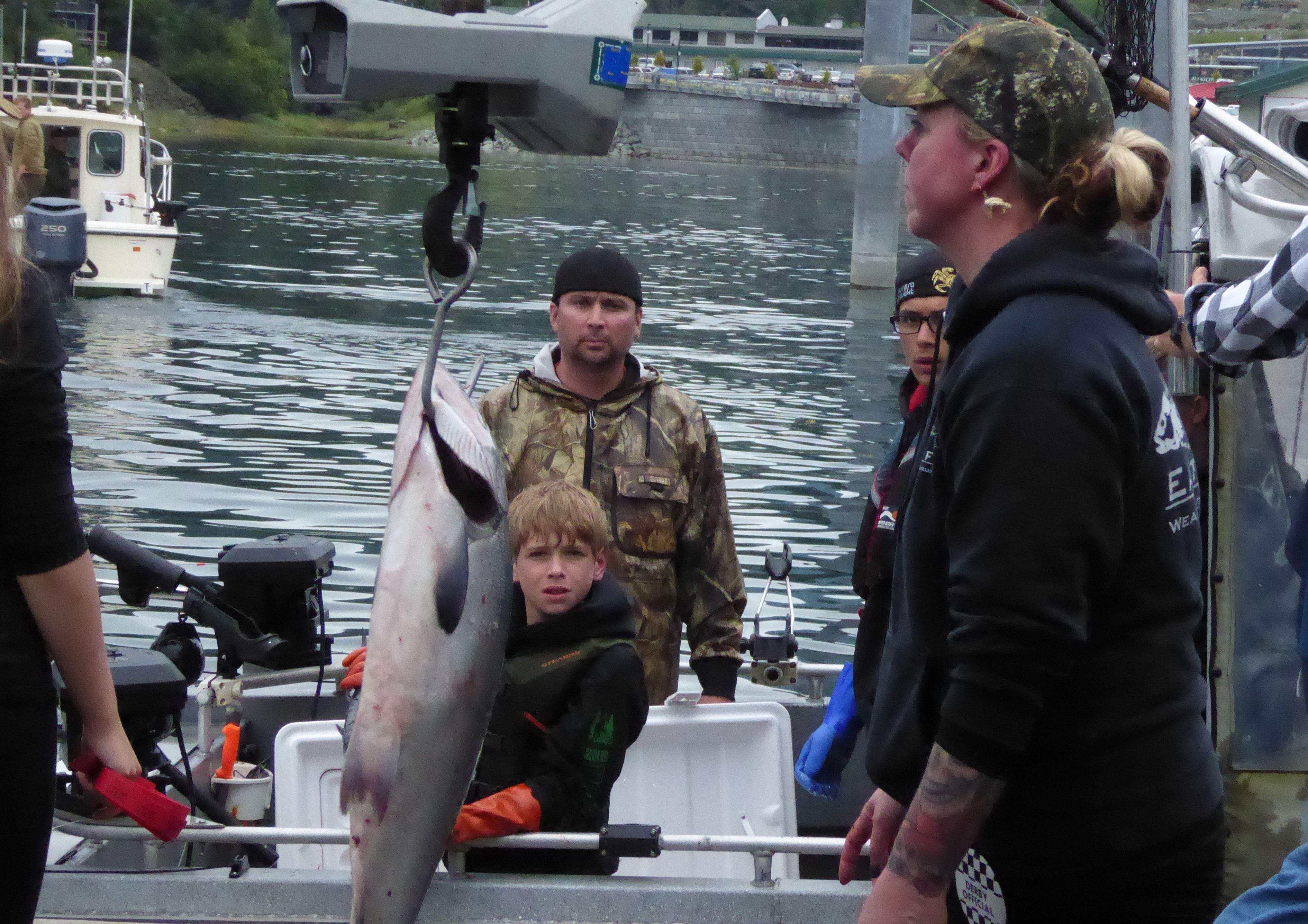 A boy and his father watch from their boat as Kami Bartness weighs their fish on a hanging scale at the Auke Bay harbor.