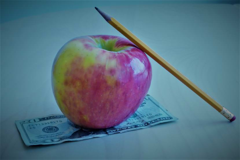 A pencil leaning against an apple sitting on top of a twenty dollar bill.