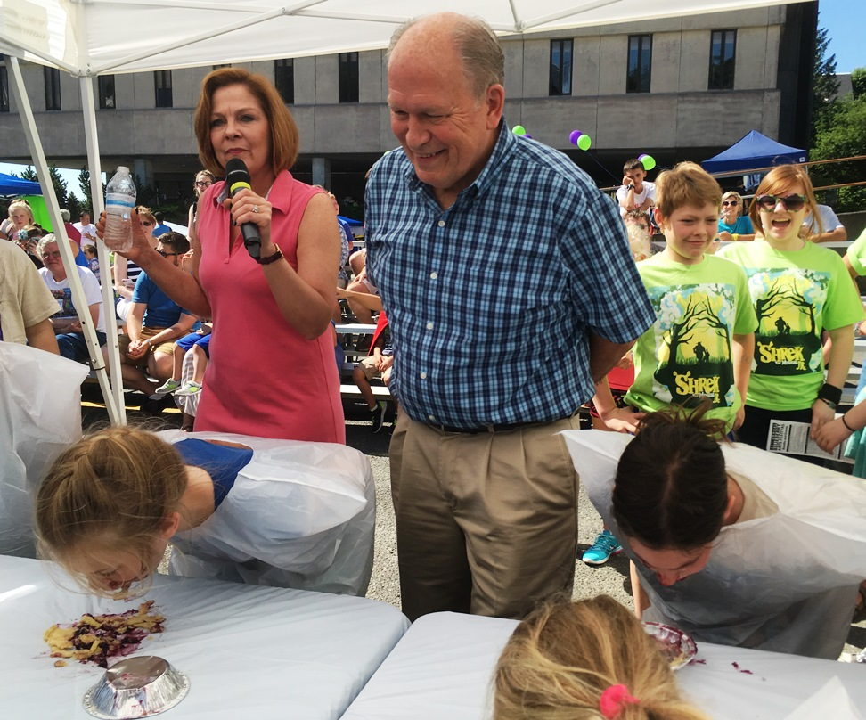 Alaska Gov. Bill Walker helps judge the Blueberry Arts Festival pie-eating contest in Ketchikan on Saturday. (Photo by Leila Kheiry/KRBD)