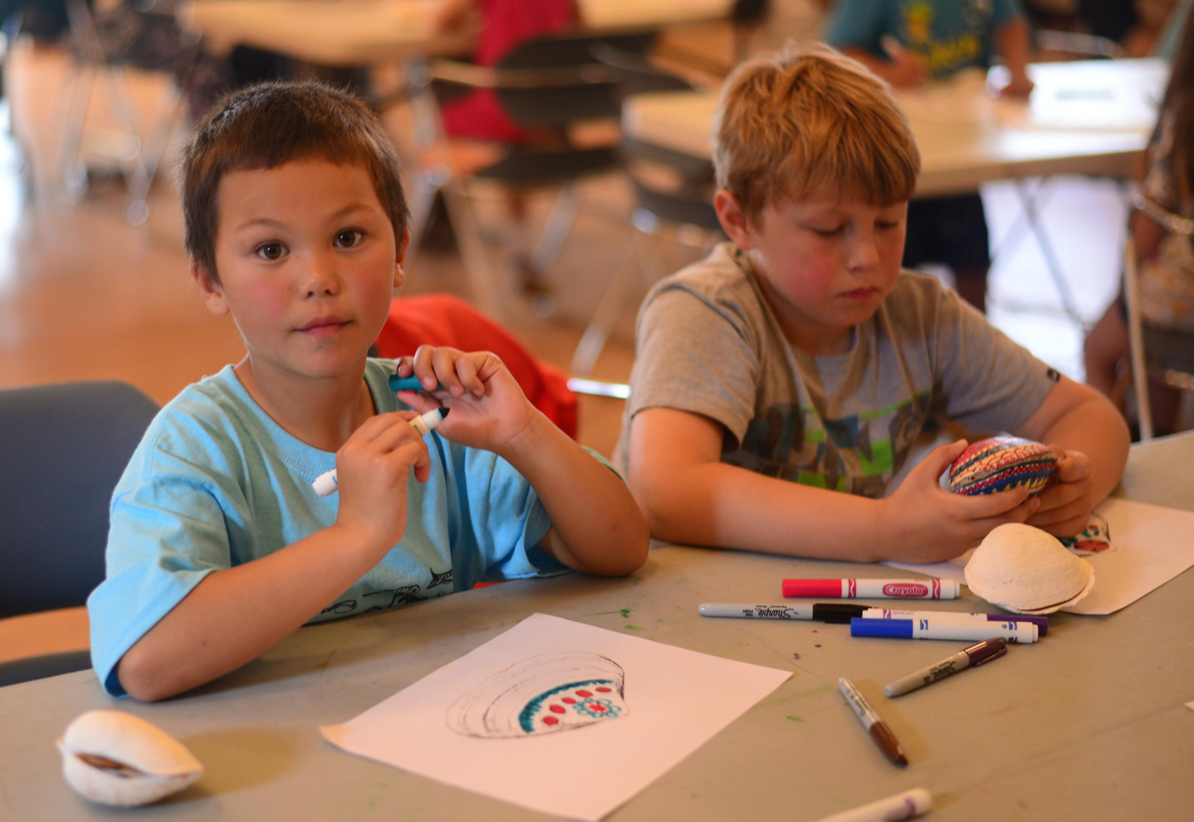 Campers draw draft clam rattle designs. (Photo by Berett Wilber/KUCB)