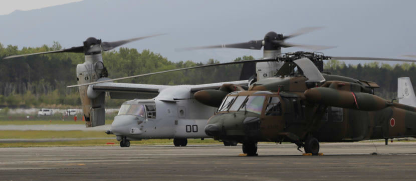 MV-22 Osprey, far left, and a helicopter on an airfield.