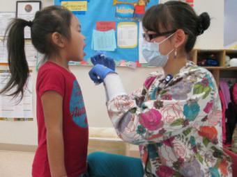 Dental health aide therapist Bonnie Johnson examining a child's teeth in the Emmonak YKHC Sub-Regional Clinic. (Photo courtesy Yukon-Kuskokwim Health Corporation)