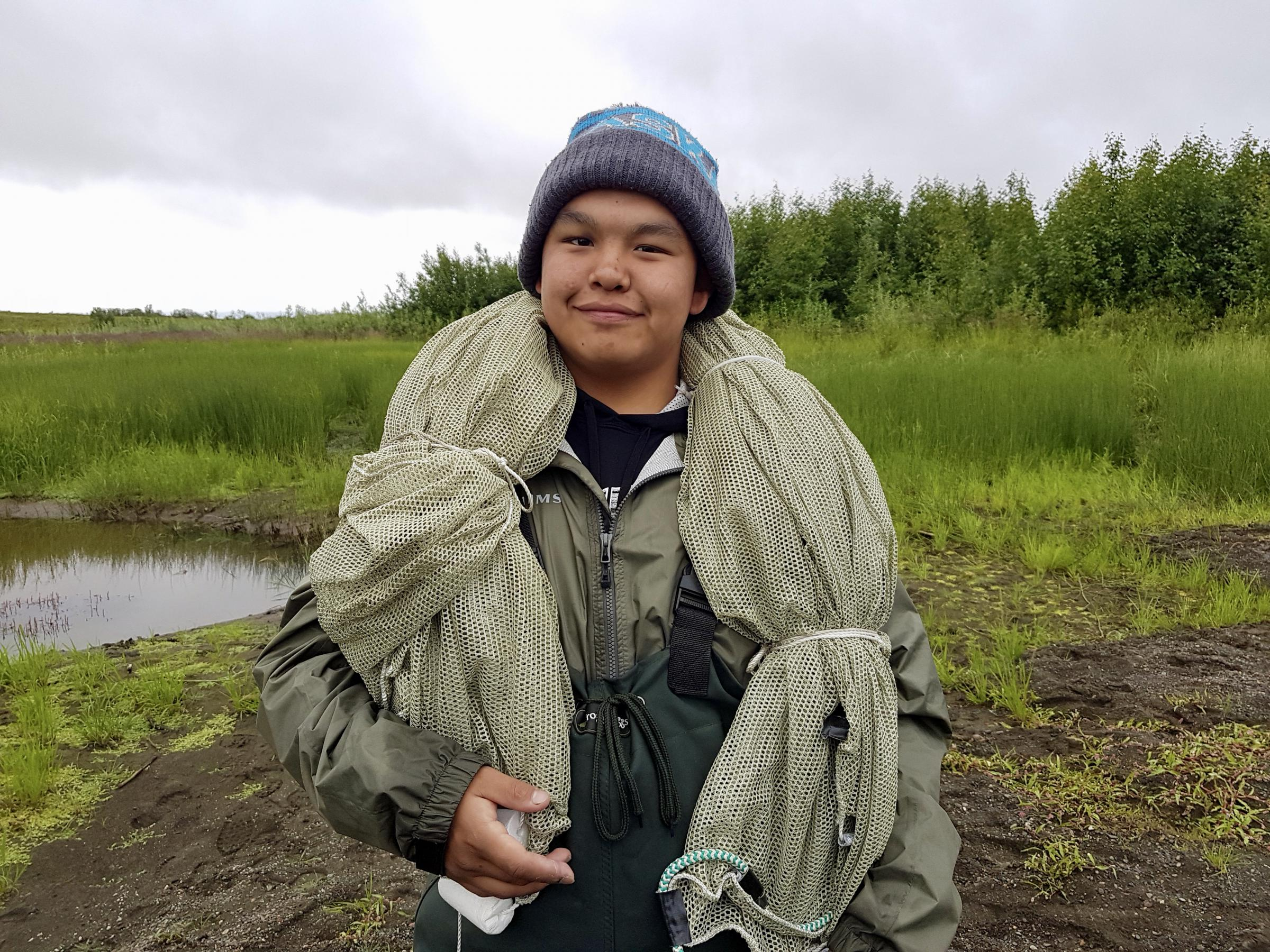 Orutsararmiut Native Council Summer Science and Culture camper Nicolai Chase, 16, gets ready to set up a beach seine net. (Photo by Christine Trudeau/KYUK)