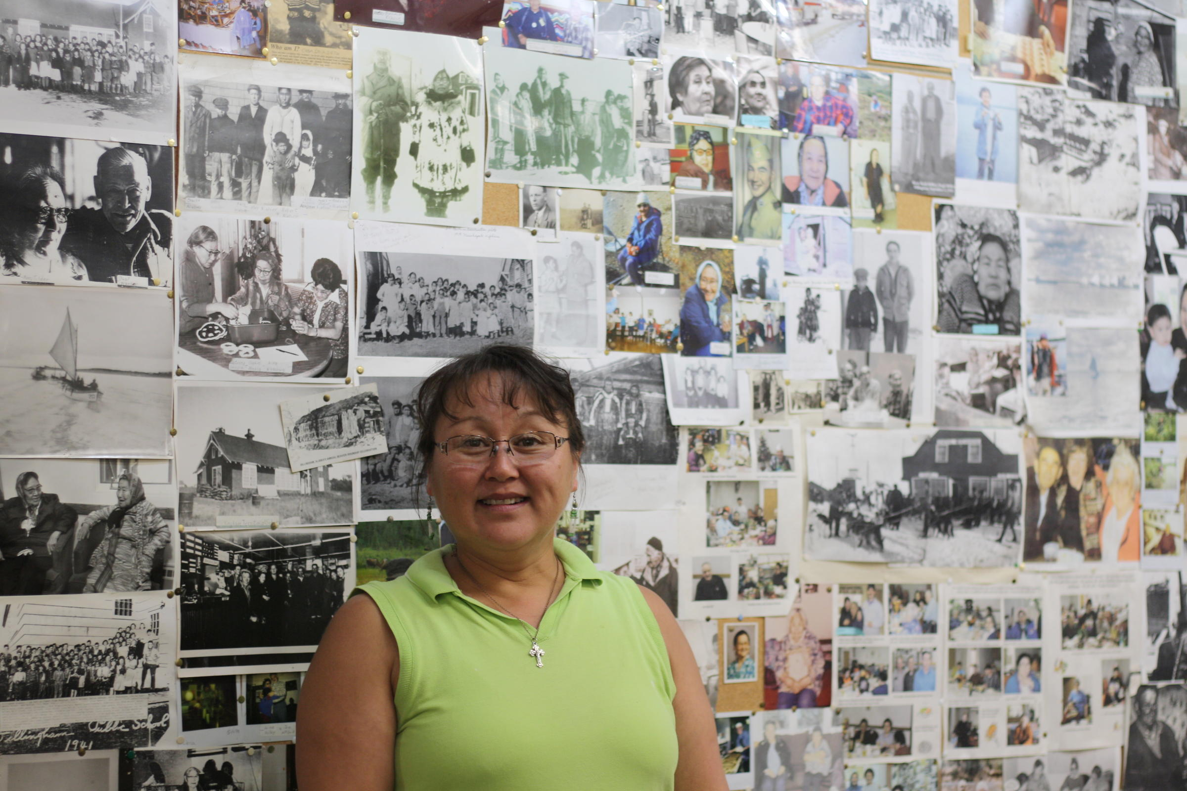 Dillingham Senior Center director Ida Noonkesser stands before a board of memories. Photos of community elders are displayed from years past. Noonkesser was recently recognized for 17 years of service at the center. (Photo by Zoey Laird/KDLG)