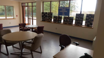 Tables and chairs in the common room with windows looking out into the parking lot
