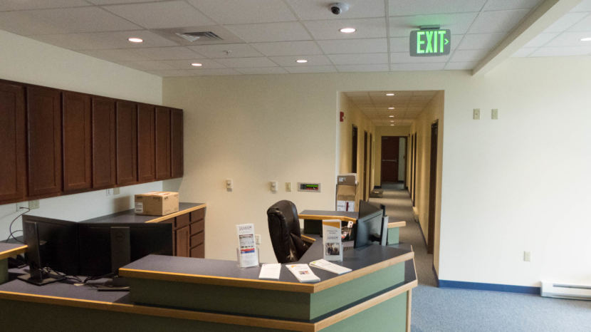 A reception desk with a hallway behind it with doors opening off it