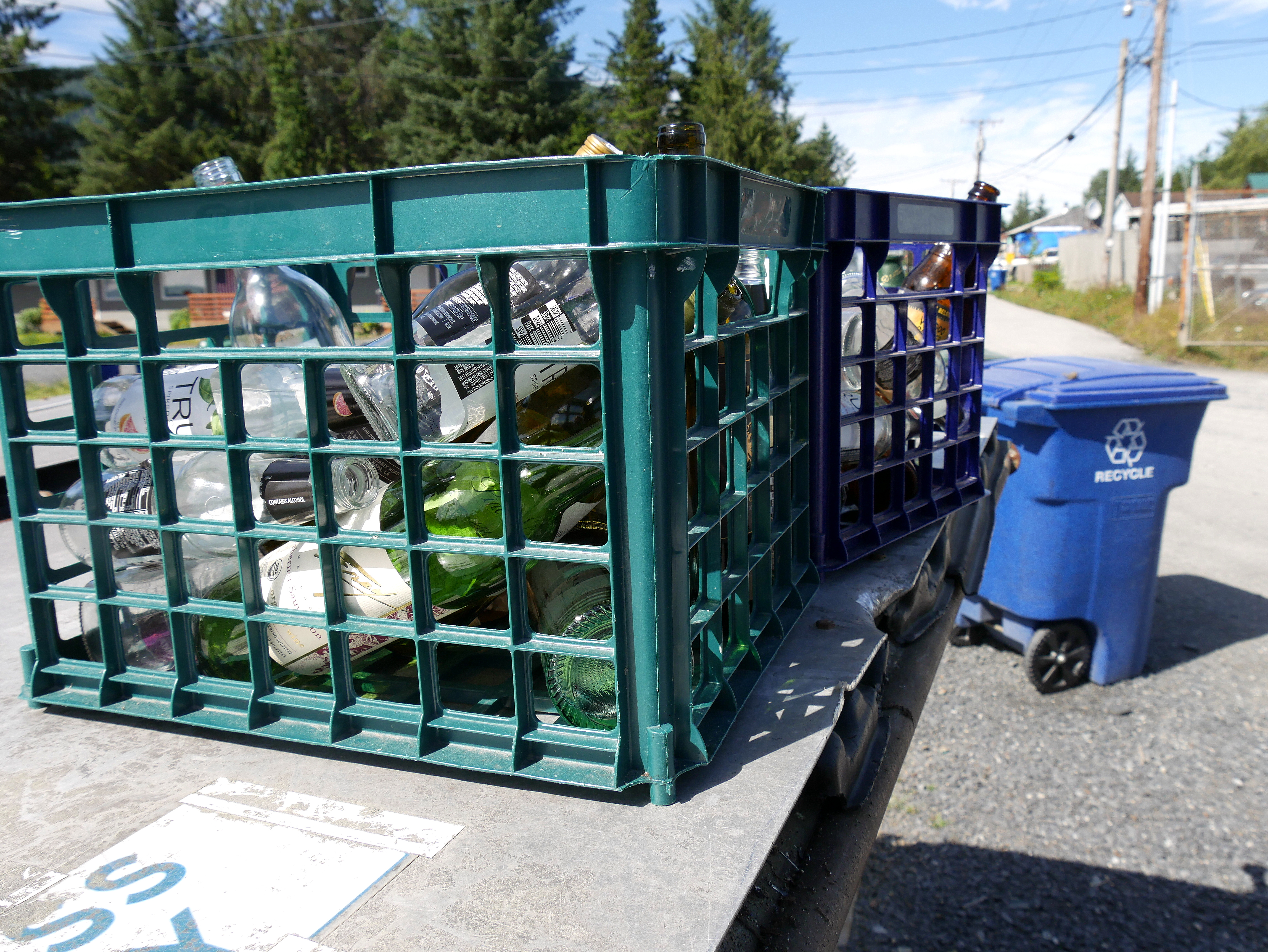 """Crates of glass bottles sit on top of a """"glass only"""" dumpster in Petersburg. (Photo by Angela Denning/KFSK)"""