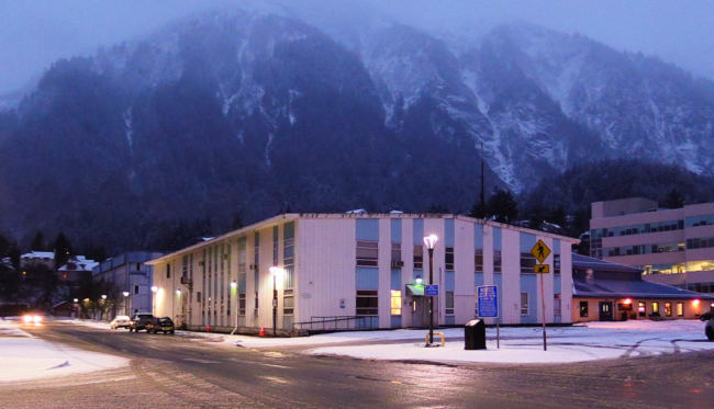 The old Alaska Department of Public Safety Building, a blue and white building, on the edge of Whittier Ave. at dusk with street lights illuminated in front of it and a snow covered mountain visible behind it