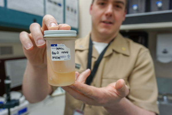 Chris Dankmeyer displays a sample of seal oil from a series of experiments working to get seal oil approved for state-licensed facilities. (Photo by Anne Hillman/Alaska Public Media)