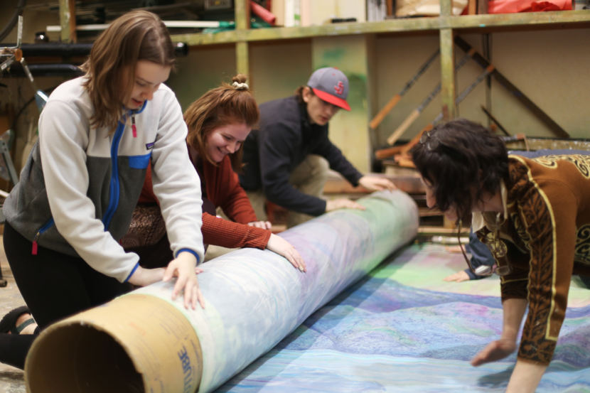 JDHS Art Club members Riley Stadt, Janessa Goodman, and Kane Ginter roll up the 2018 Alaska Folk Festival backdrop with adviser Heather Ridgway. (Photo by Annie Bartholomew/KTOO)