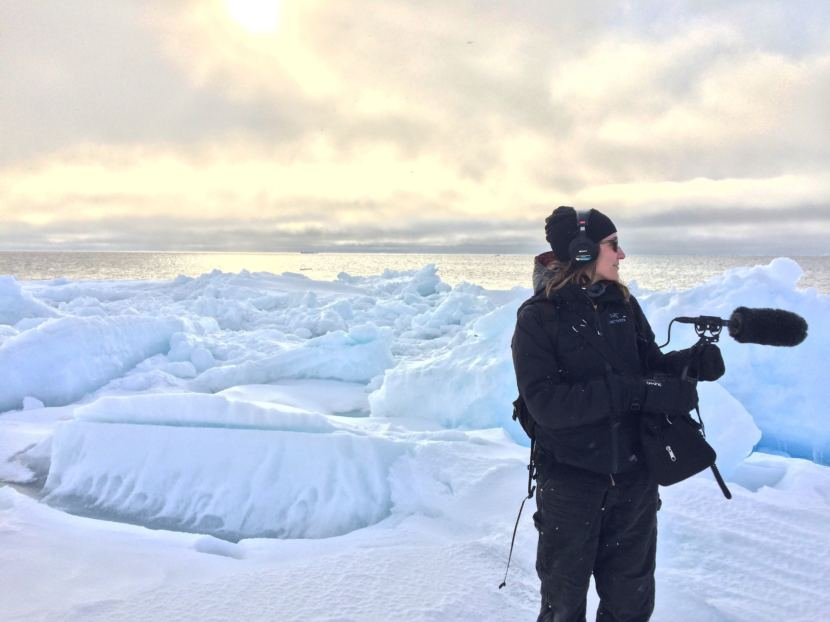 Ravenna Koenig of Alaska's Energy Desk/KTOO stands on the leading edge of the sea ice while recording sound for a story about Arctic Field School. (Photo courtesy of Lindsay Cameron)