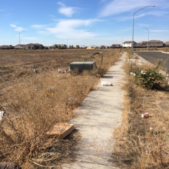 This photo shows the sidewalk littered with garbage in a semi-abandoned subdivision in Stockton, California (from The Atlantic)