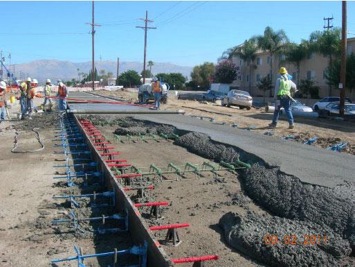 Obreros de la construcción ponen concreto sobre la superficie de lo que será el carril exclusivo de autobuses en la extensión Canoga de la Línea Naranja del Metro. (Foto Metro Construction).