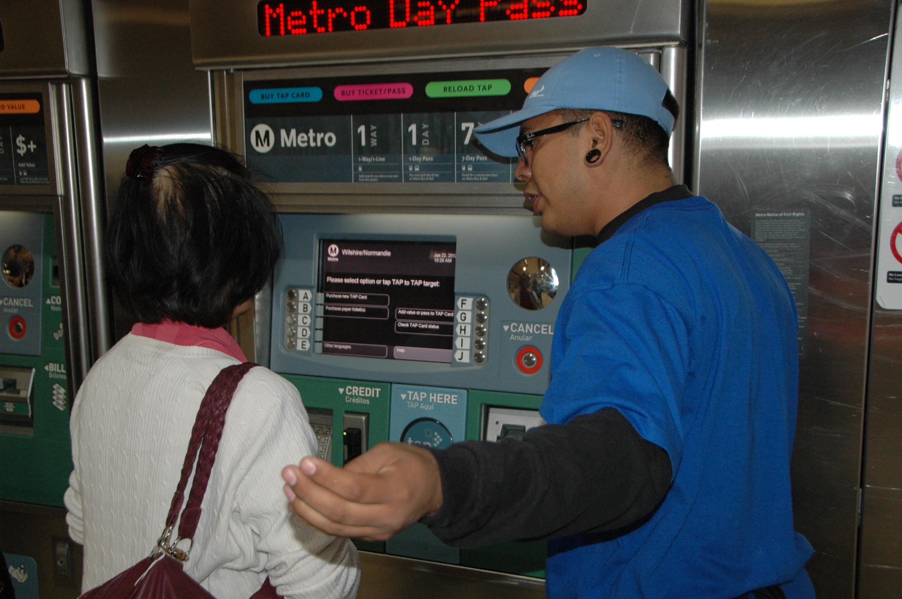 Empleado de Metro ayuda a una persona a comprar la tarjeta TAP en la estación Normandie de la Línea Morada del Metro.