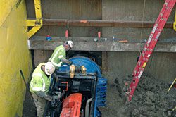 Workers use a diesel engine mounted on a short track to extract another auger from the new tunnel under Wilshire Bl.