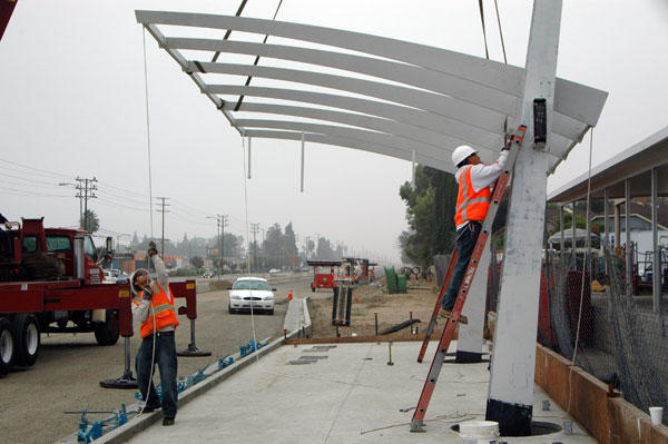 North view of Roscoe Station canopy construction. Metro Orange Line right-of-way in the background.
