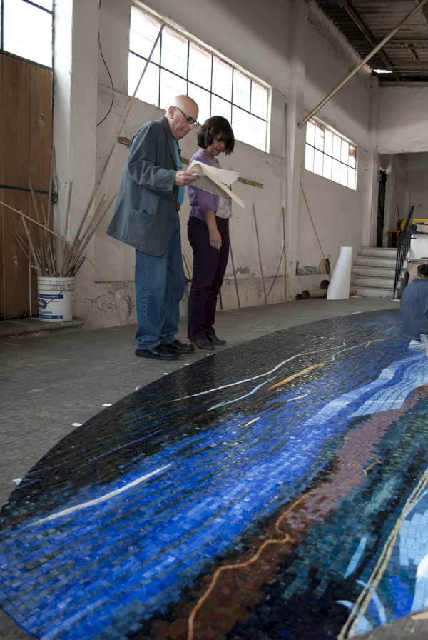 The artist inspects the finished mosaic artworks