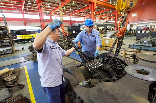 Fuyuong Chung, at right, and Josue Moir prepare to lift a Power Truck for installation on a Light Rail Vehicle