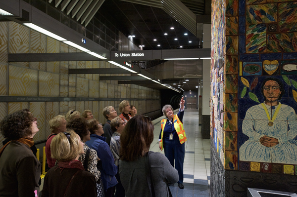 A Metro Art tour guide discusses the artwork at Universal City Station. The ceramic mural by Margaret Garcia, called Tree of Califas, marks the historic site of the Campo de Cahuenga, where in 1847 Mexico relinquished control of California to the United States.