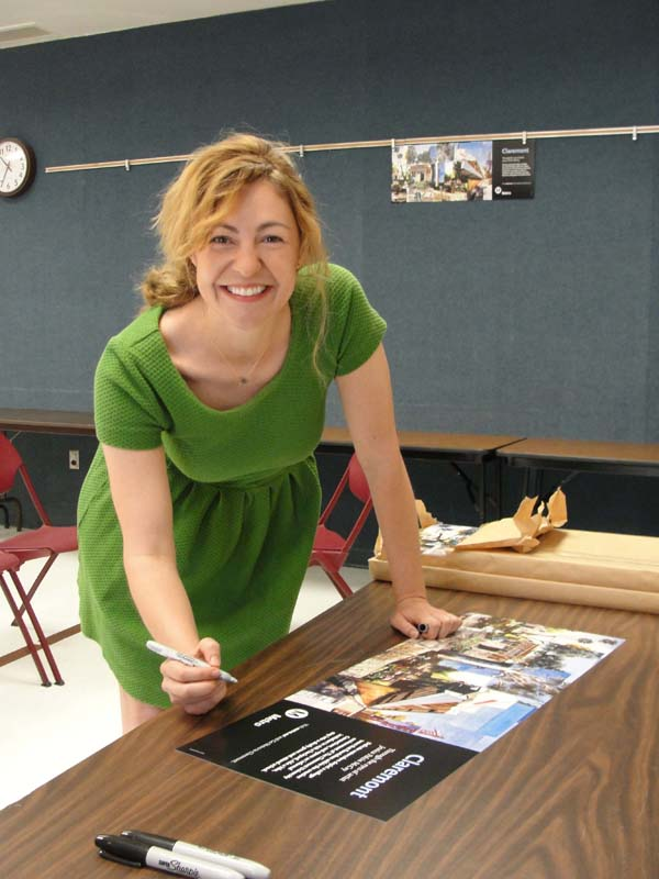 Artist Jessica Polzin McCoy signs free copies of her poster celebrating the city of Claremont on May 31 at an event at the Claremont Public Library.