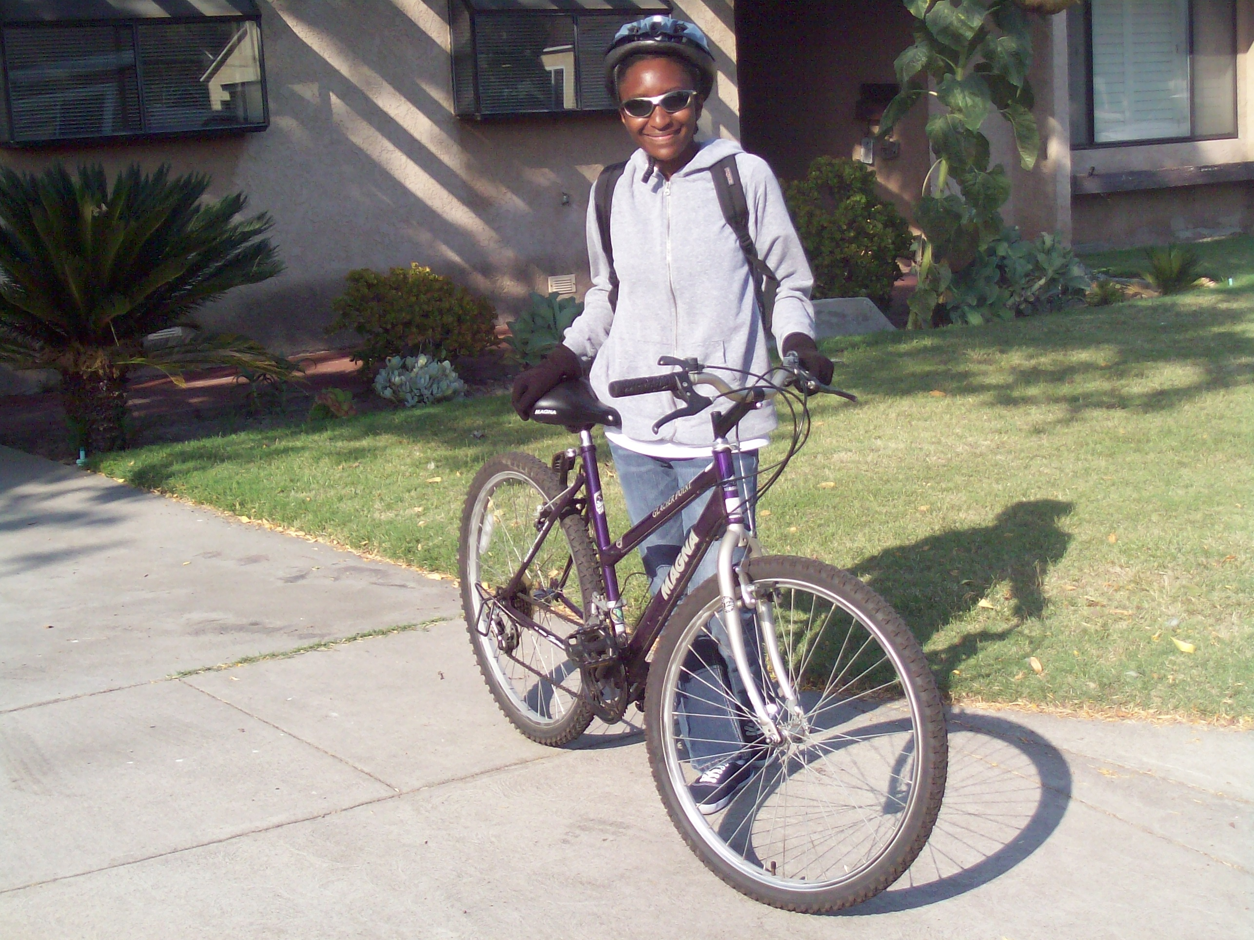 Breeanna with her mountain bike, helmet, and sunglasses getting ready to bike to work. Photo courtesy of Breeanna Taylor.