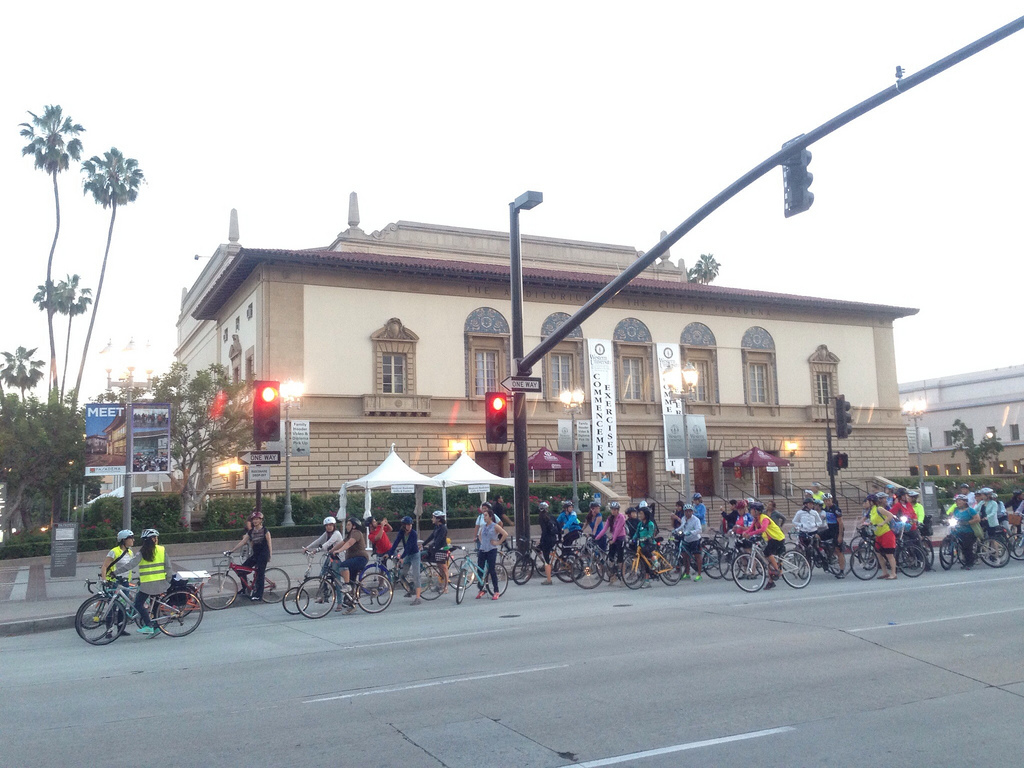 Maria guides several dozen bicyclists in front of the Pasadena Civic Auditorium.