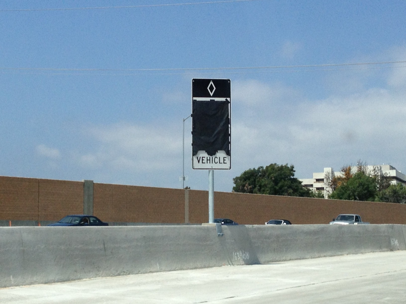 Contractor gets ready to open new carpool lane segment with installation of HOV signage at the freeway median.