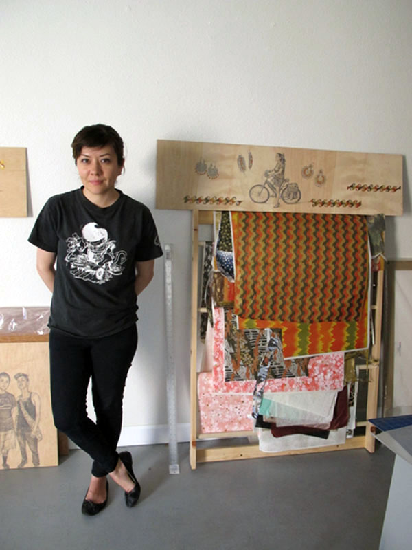 Artist Shizu Saldamando in her studio, with one of her original artworks in the background.
