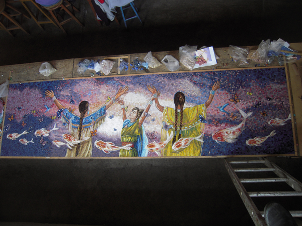 A view from above of an artwork panel completed by artisans who hand assembled thousands of mosaic pieces and pictured in nearby bags. Photo courtesy Perdomo Studio.