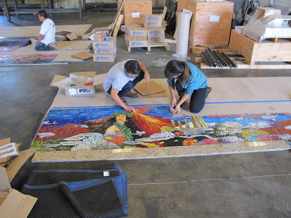 Metro Art Manager Angelene Campuzano, assisted by Metro Art Intern Janet Le, carefully inspect the artwork panels from the fabricator at the workshop in L.A. where they will be assembled into painted steel framed panels and readied for delivery to the station.